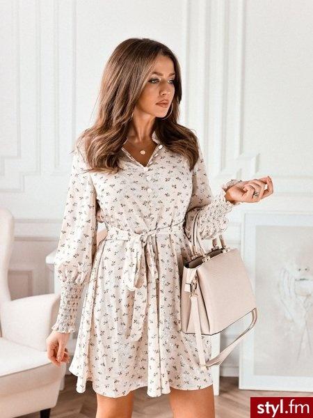 Dodaj opis (max. 250 znaków)Sukienka wykonana została z lekkiego materiału pokrytego pięknym, subtelnym wzorem. Kołnierz oraz ozdobne guziki dodają całości elegancji. Wszyty pasek pozwala na dopasowanie sukienki od figury. https://roseboutique.pl/ - Dzienne Sukienki Moda